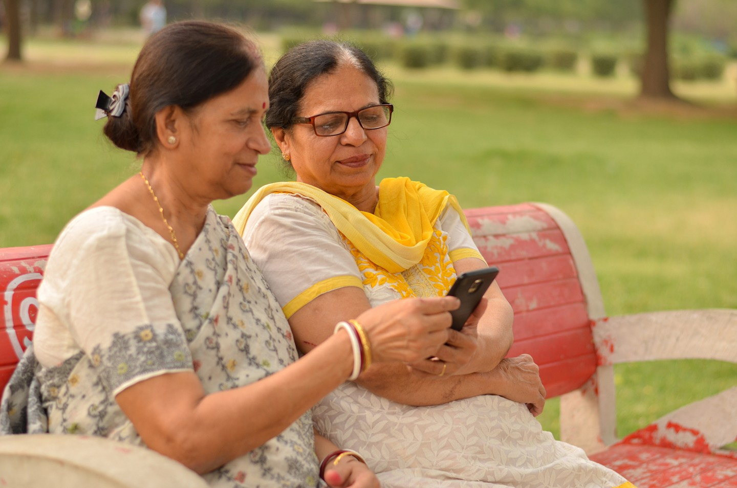 Indian women sharing a phone